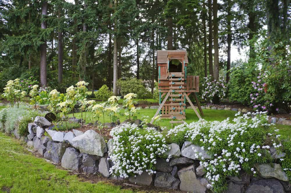 Small play fort in backyard set among gorgeous gardens.