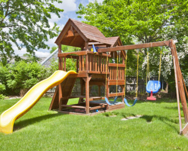 Beautifully manicured backyard with large two story playhouse with yellow slide and two swings.