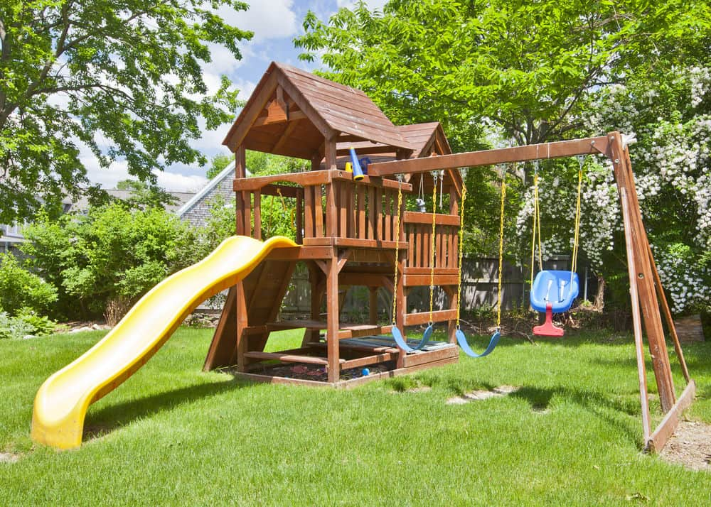 Beautifully Manicured Backyard With Large Two Story Playhouse Yellow Slide And Swings