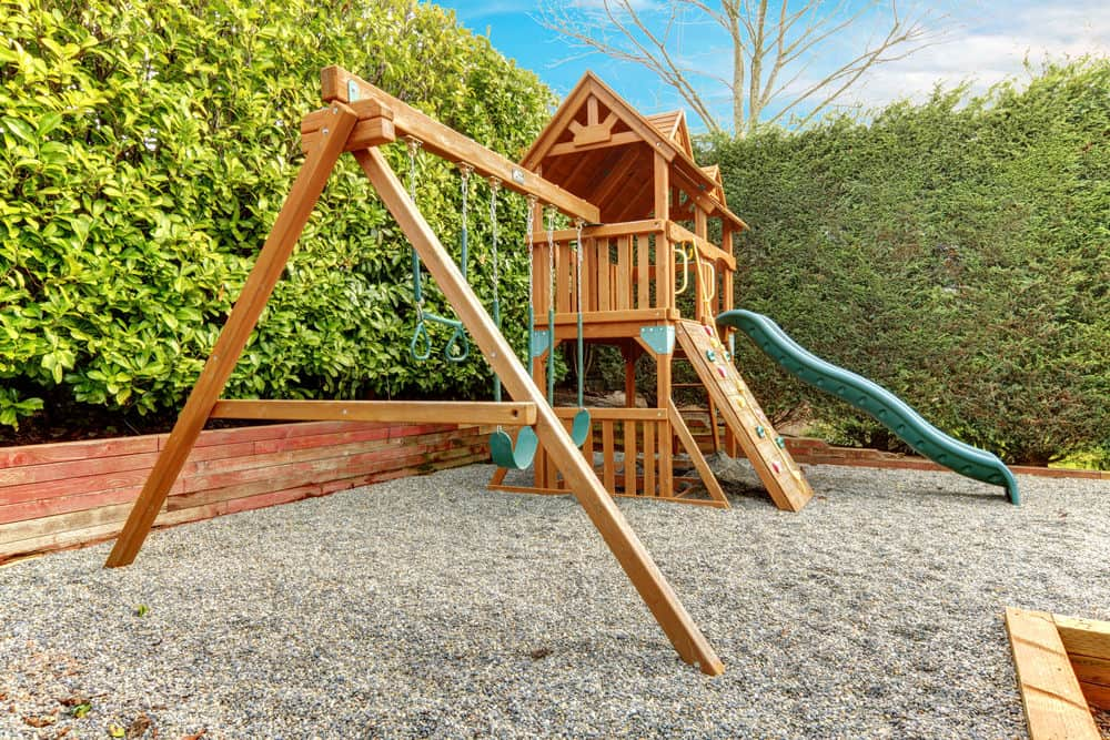 Large wooden playground with fort, climbing wall, green slide and swing set in private backyard.