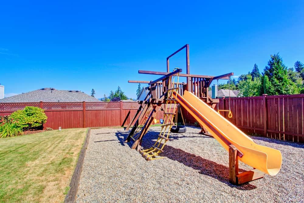 Backyard playground on pebble surface with long yellow slide.