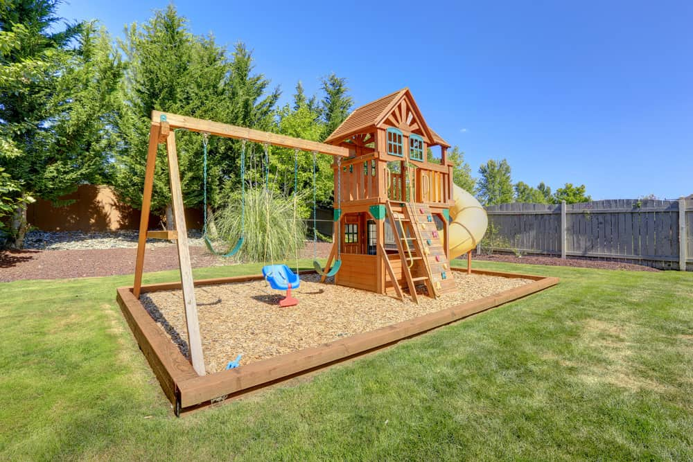 Play fort with ladder and fun lower playhouse with swing set in backyard.