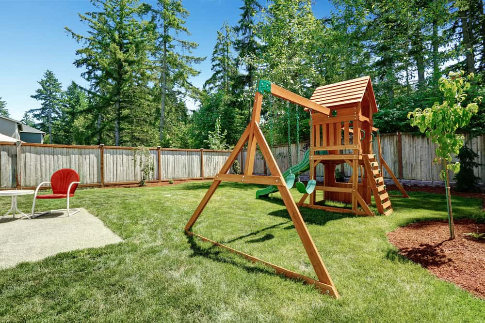 Wooden playground with elevated play fort, ladder and two swings.