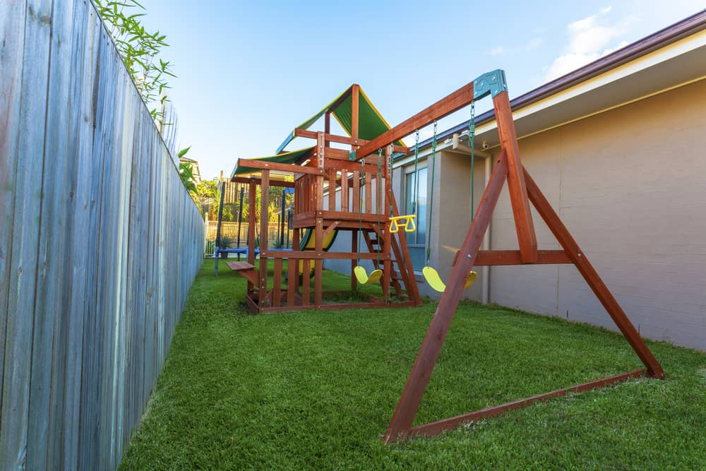 Large wooden playground swing set and fort in small backyard.