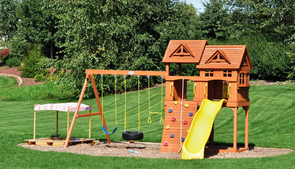 Wood backyard kids playground with climbing wall, tire swing, yellow slide, regular swings and playhouse.