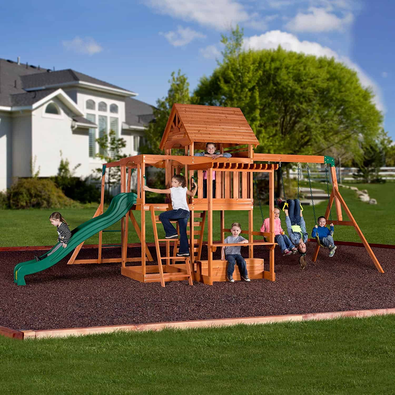 Large two story playhouse playground with slide, deck and swing set.