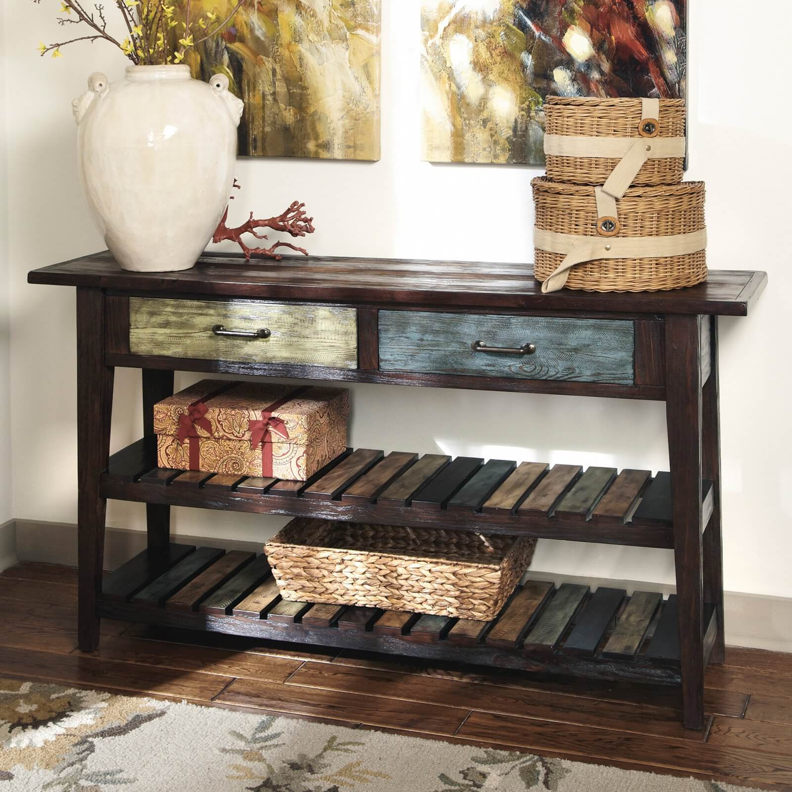The drawers of this lightly distressed table are painted light green and light blue, contrasting with the dark, natural wood of the rest of the table. The two lower shelves are covered in multi-colored slats.