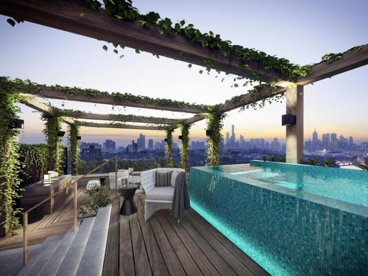 This infinity edged pool creates a relaxing atmosphere of this rooftop patio area. The overgrown trellises balance out the use of concrete and decking, adding color to balance the aqua blues of the pool.