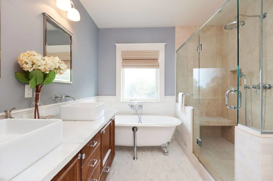 This lovely bathroom is decorated in a beautiful palette of colors that complement the narrow space. The glass enclosed shower is all done in creamy, tan marble which is offset by the white in the rest of the bathroom. Rich wood contrasts the entire room, while powder blue walls bring everything together.