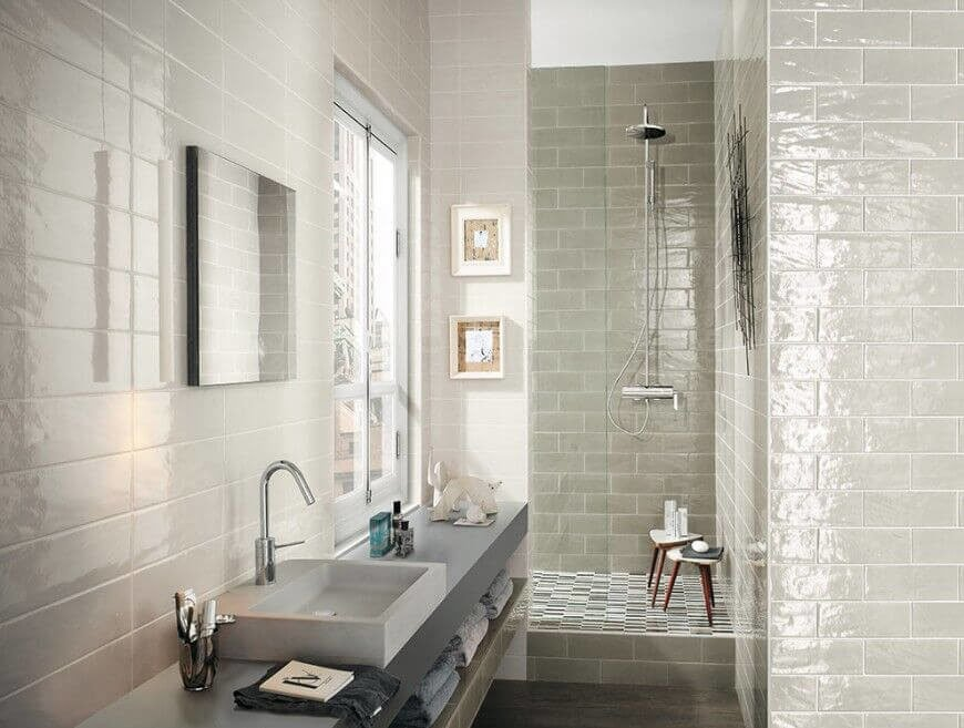 Glossy tile walls help to brighten up this angular space. Including a long, narrow vanity gives extra functional space, and storage, in an area that otherwise would go unused.