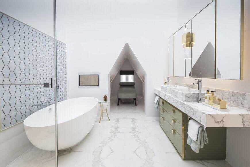 Vaulted ceilings make this bathroom feel massive. Gold accents complement the olive green of the vanity drawers. White marble and delicately patterned wall art break up the use of white while also maintaining the airy feel of the room.