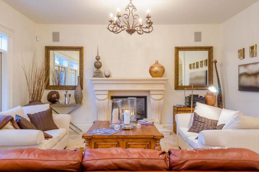 Viewed head-on, we see that the prior living room is all about symmetry, with a pair of gold framed mirrors flanking the central fireplace and the white sofas standing in corresponding positions next to the rich wood coffee table.