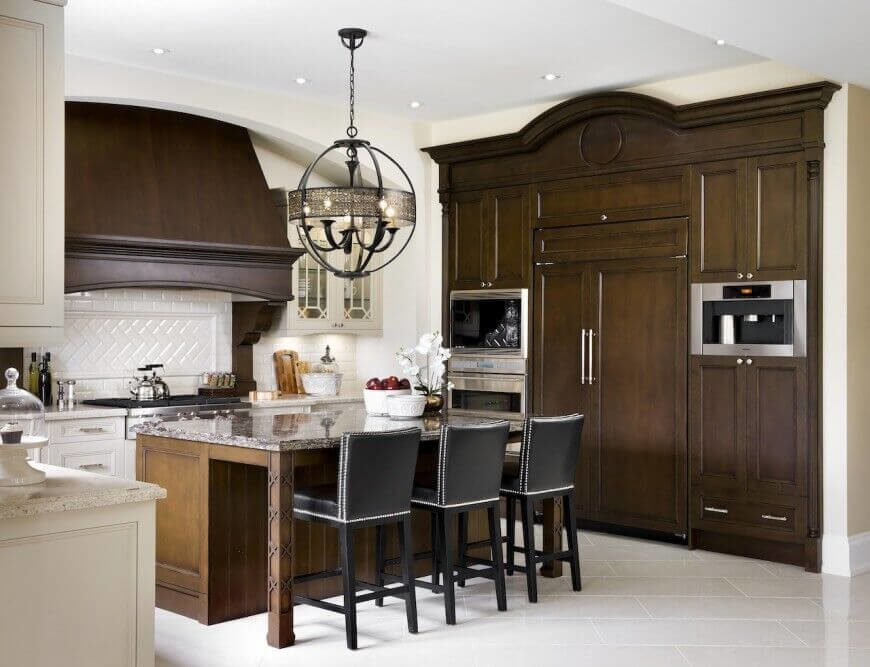 Bold, dark wood is the staple piece of this room, with a dash of white to show off the lovely finish of the wood. Silver and black accents liven up the room and the chandelier over the island is a sight to behold.