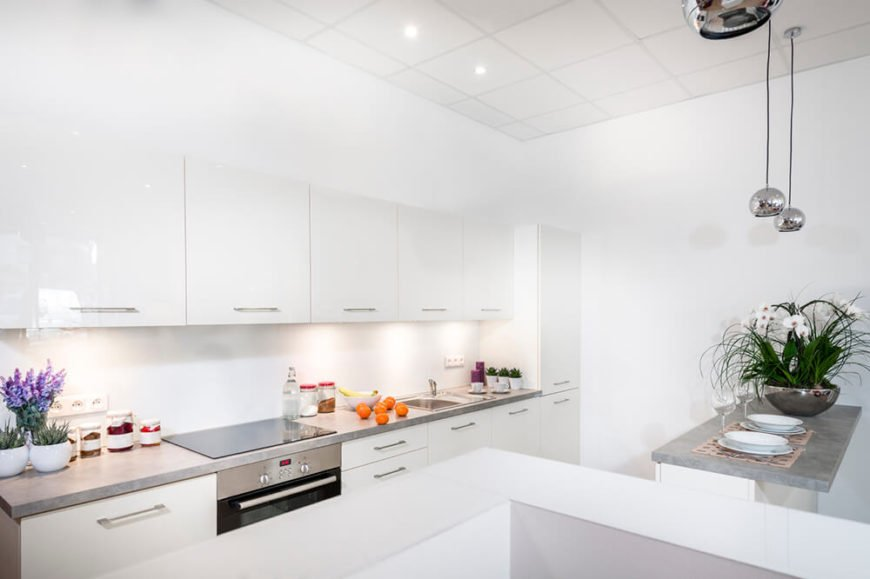 A stunning and pristine white kitchen with minimalist cabinetry, a tiled ceiling, and a small eat-in island with a contrasting light gray countertop. Chromed pendant lighting adds visual interest to this minimalist design. Color is added back into the design with accents and houseplants.