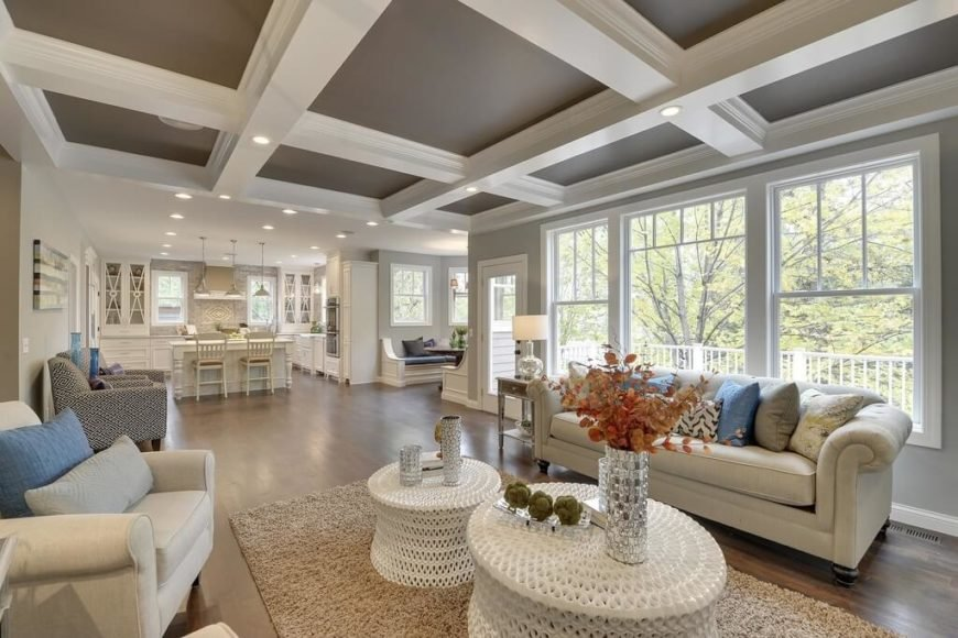 As part of a larger open plan space that includes a kitchen and dining room, the living room features subtly off-white sofa and armchairs hugging a pair of textural circular coffee tables in white. Above, a white coffered ceiling mirrors the look of the room.