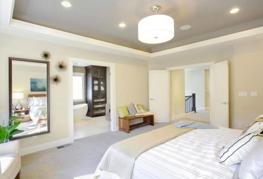 In a bright off-white bedroom, we see that French doors aren't always used strictly for patio access. Instead, the set here creates a broad opening that helps a sense of slow into the primary bedroom suite.