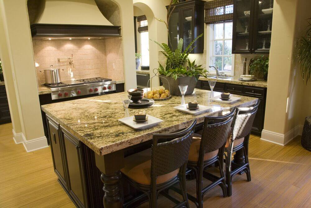 Chairs continue the color scheme of the room with dark wood and neutral tan seats. The island is large enough to offer plenty of space for cooking prep and double as a breakfast bar for three. Beige walls accent the dark cabinets and the granite counter top well.