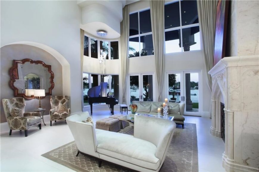 A modern design is prevalent in this living room, with a unique double-backed chaise sitting near the marble stone fireplace. Near the back of the room, you will see two upholstered designer chairs sitting before a large mirror. The wall follows a curve and wraps around to face a backyard and waterfront.