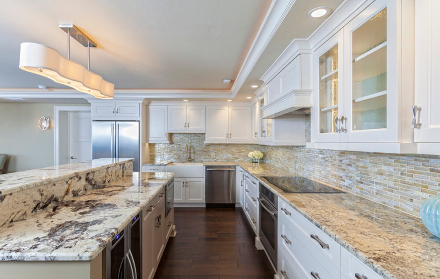 A beautiful contemporary kitchen with white cabinetry, stainless steel appliances, a multi-colored glass mosaic tile backsplash, and mismatched granite. The granite on the island has a much larger vein of gray, which provides an interesting contrast to the much more sandy granite of the main stretch of countertops.