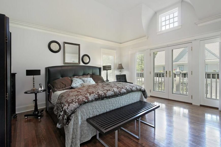 This vast bedroom stands a vaulted ceiling and white walls over rich hardwood flooring. Dark furniture heightens the contrast, naturally lit via a large set of windows and pair of glass French balcony doors.