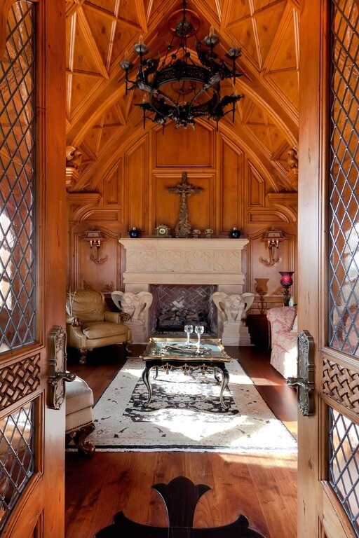 This living room is saturated with rich wood grain, from the top of the ceiling to the hardwood floor. A grand fireplace features two gargoyles and a dark tile interior. The wall behind the fireplace features a symmetrical design and is accented by the large cross and other small decorations.