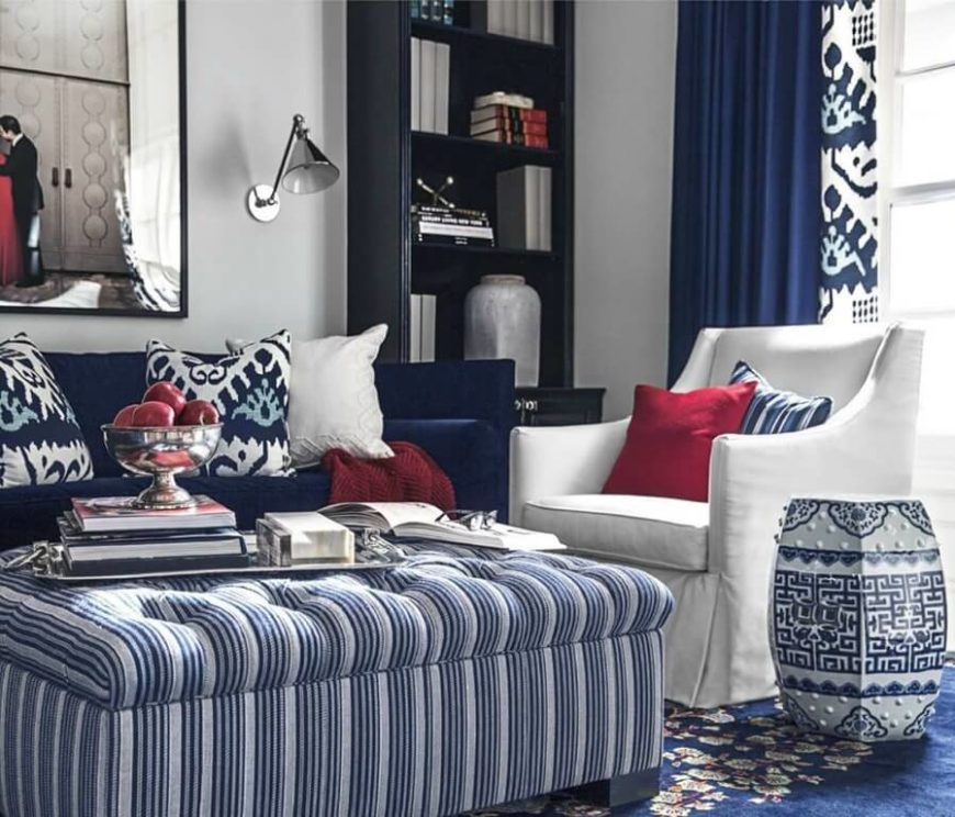 A unifying color scheme of blue and white pulls this living room together, centered on a large button tufted ottoman. The blue sofa is complemented by a white armchair at right.