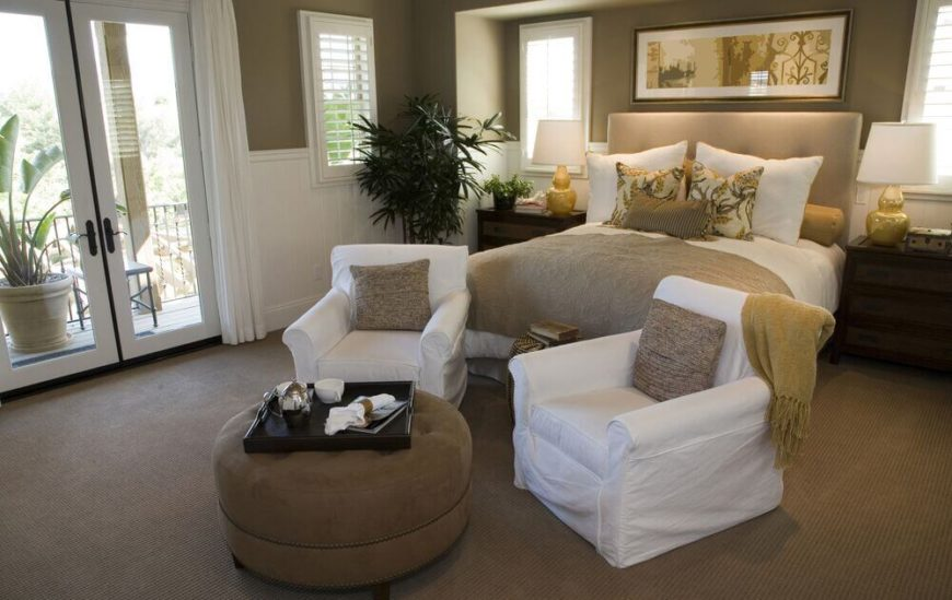 This bedroom features an elegant mixture of light brown and white tones, including a pair of white club chairs and brown button tufted ottoman. White framed glass French doors allow for upper level balcony access.