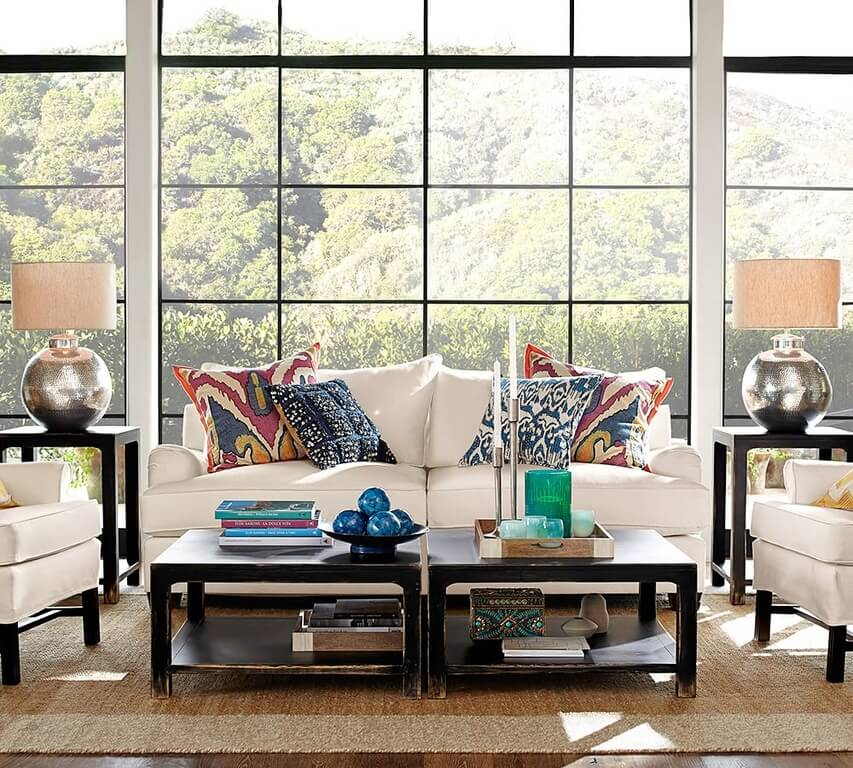 Standing beneath a set of full height windows, we see a white sofa and pair of matching roll arm chairs centered on a beige area rug in this living room. A pair of rustic dark stained wood coffee tables offer contrast and utility.