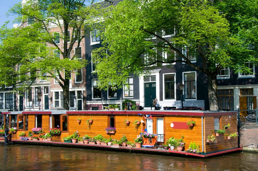 An enormously long houseboat with wooden siding and tons of garden containers throughout. This lovely permanent home is one of 2,400 in Amsterdam.