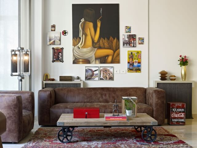 This living room is set in a small space, with unique decorations everywhere. The large painting of a woman is the focal point of the space, while other painting and photographs cover the wall and keep this space feeling lively and modern.