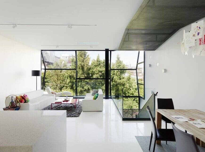 This living room, at the top level of a unique modern home design, is awash in bright whites from the sleek flooring to the ceiling. A pair of white minimalist sofas face off over a bold red coffee table in sunlight through full height glazing.