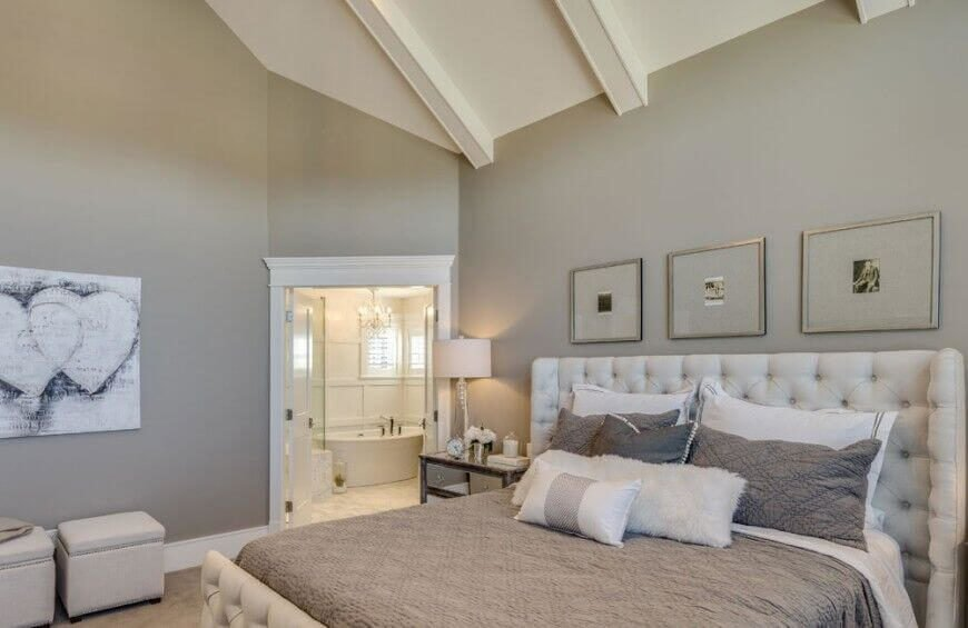A white vaulted ceiling with painted exposed beams hangs above a neutral hued bedroom with white button tufted headboard. White French doors lead to a bespoke white bathroom.