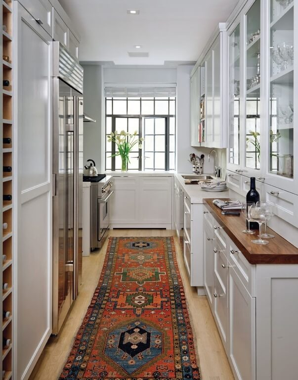 A slim galley kitchen with a built-in wine rack and pantry next to the stainless steel refrigerator. Glass-front cabinets house the more delicate glassware, and a cabin-style runner runs the length of the kitchen.