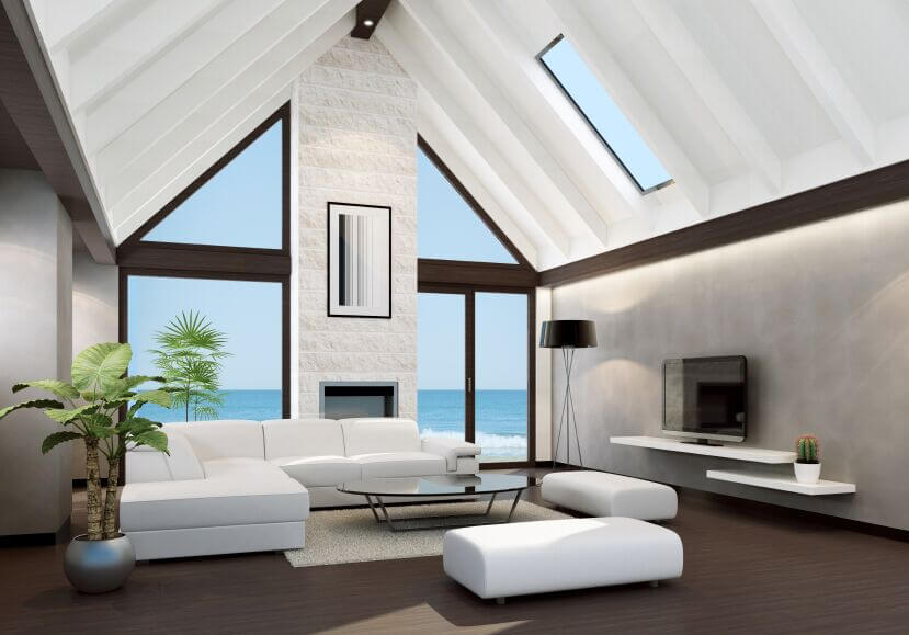Beneath a soaring vaulted ceiling, we see a sleek modern white sectional wrapping around a minimalist glass-top coffee table. The white brick fireplace is flanked by massive full height windows for a naturally bright appearance.