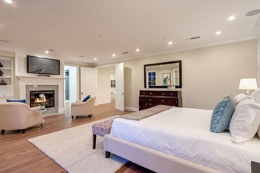 This vast primary bedroom en suite features an expanse of rich hardwood flooring, and opens to the rest of the home via French doors for a truly expansive entryway.