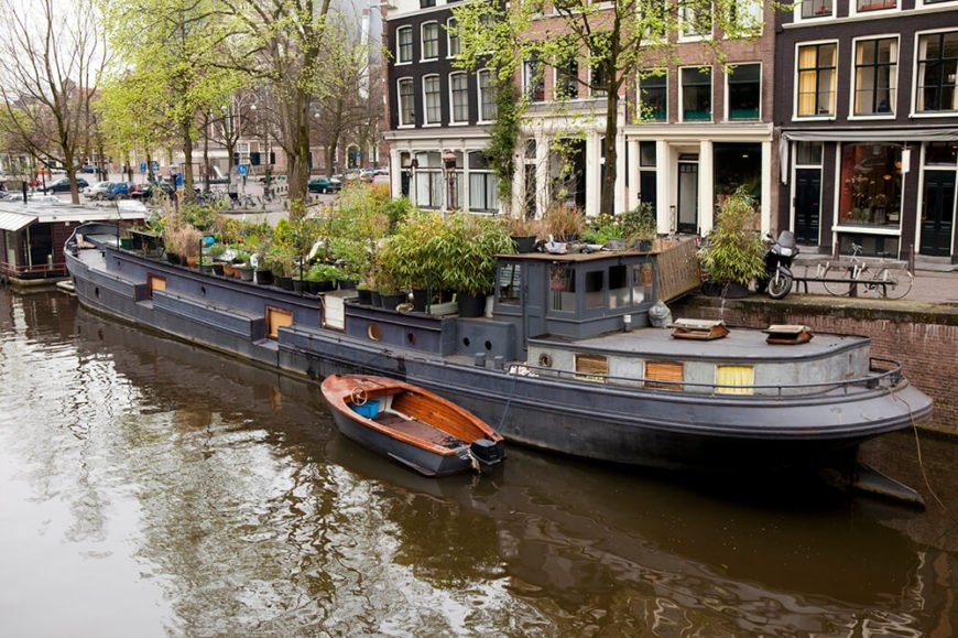 Another large ship-like houseboat located in Amsterdam. the top of the boat is filled with various potted trees.
