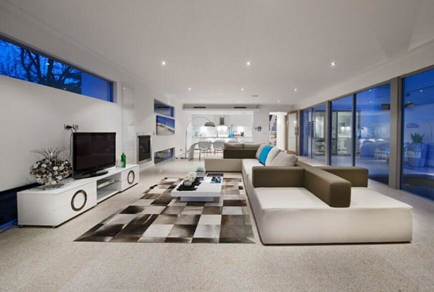 In a vast living room decked out from end to end in modern minimalist style, we see a uniquely crafted sectional in white and light brown. This piece dominates the room, reflecting the color of the patterned area rug at center.