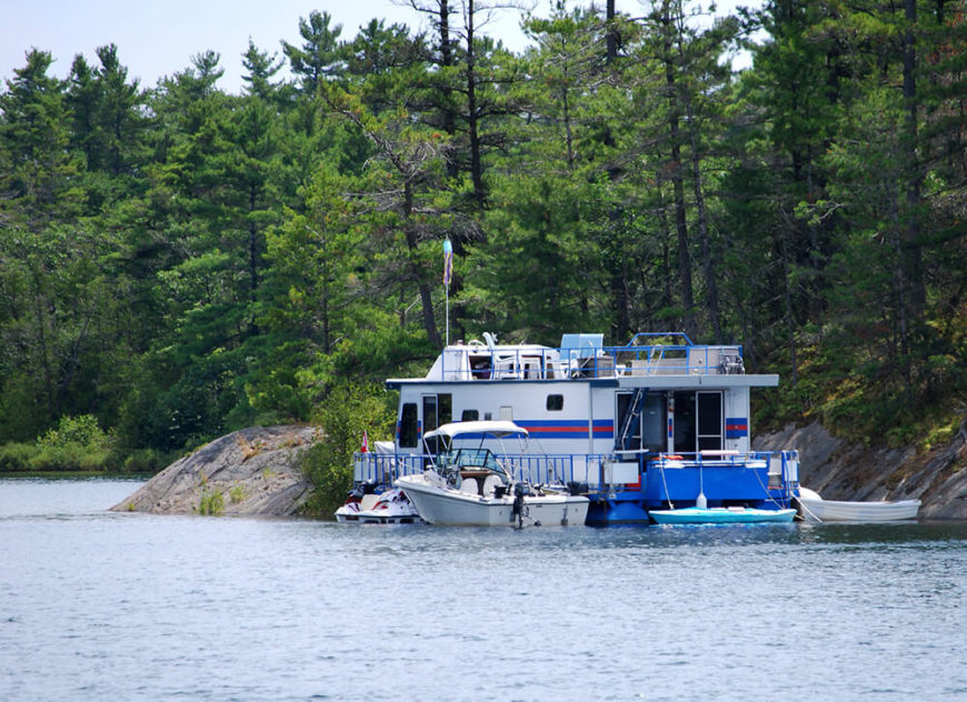 A massive houseboat with a variety of other boats moored to it off the coast of a forested island. This is a perfect example of house boating for leisurely purposes.