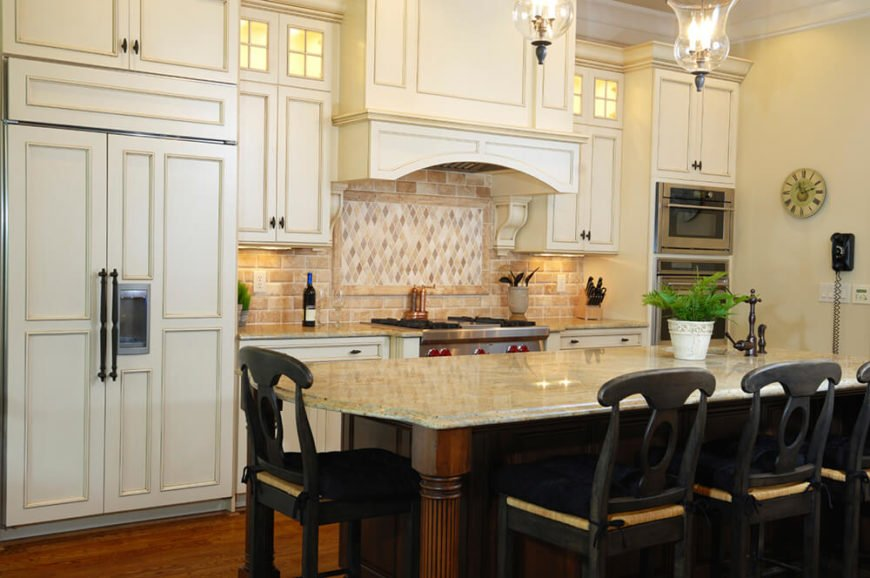 To balance the creamy, off-white cabinets, a dark wood island and even darker chairs were introduced to the room. This design element helps to ground the space and keep it from feeling too bright while also offering visual interest in a drastic change in colors.