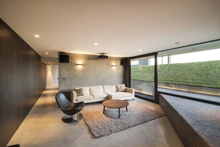 In this lower level living room filled with natural light via full height glazing, we see a lone white sectional standing against a concrete wall in soft grey. Paired with a natural wood coffee table and black leather club chair, the sectional offers a bright point of interest in the room.