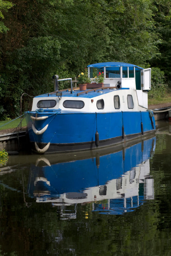 A large houseboat in bright blue and contrasting white moored off of a canal. Unlike many other houseboats, this one has very few windows and no open