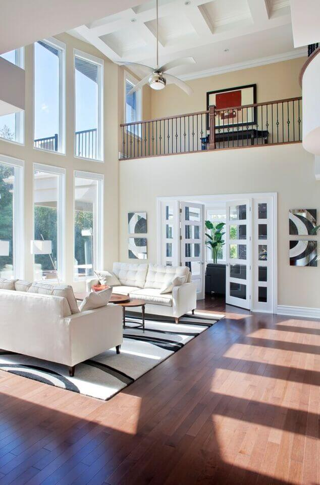 Sitting beneath a soaring two-story set of windows in the bright light of day, we see a pair of contemporary white sofas facing off over a black and white rug on hardwood flooring.