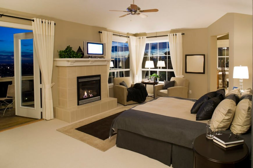This primary bedroom en suite features doorless bathroom access plus large windows and a set of French balcony doors. The fireplace at center is wrapped in beige tile, perfectly matching the wall tone.