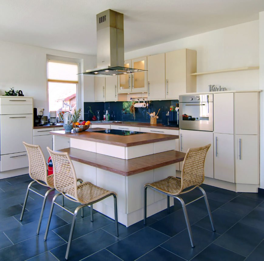 Bold blue tiles are enough to brighten up this space, so much so that the rest of the design can remain natural wood hues and white cabinetry. Separating the island cook space from the eating space of the counter is a genius idea and it allows the individual spaces to remain uncluttered.