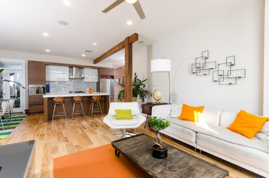This bright living room features a kitchen and dining room opening, with stark white walls and a light golden hardwood floor. To accent the space, you will see vibrant accent pillows, and square wall decorations that hold small candles.