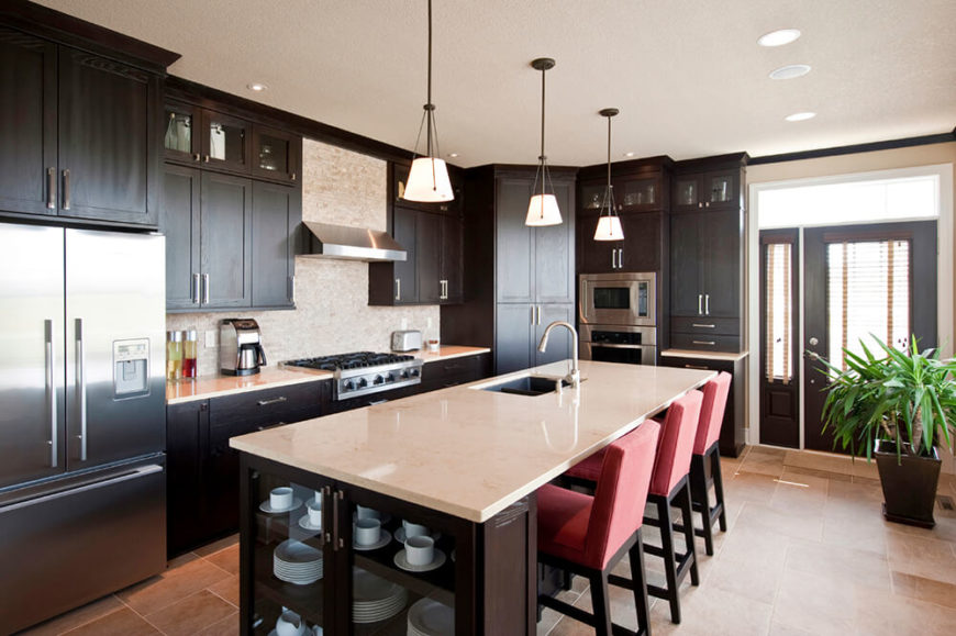 A balance of light and dark is important in narrow spaces like this. The kitchen work space is kept to a single aisle surrounded by dark cabinets but effectively balanced by the creamy countertops and matching tile backsplash. The red chairs bring a fun hint of color to the room.