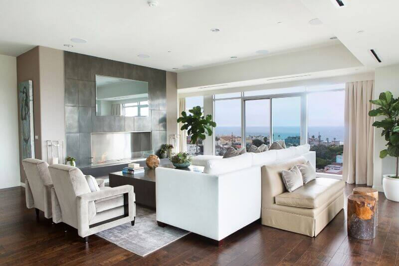Clean lines and sleek surfaces abound in this modern living room, bathed in sunlight through full height windows. A large white sectional dominates the furniture set, complemented by beige armchairs and a small leather love seat.
