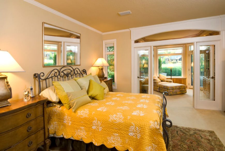 This large primary bedroom en suite features a set of glass French doors dividing the more private sleeping quarters from a family-room styled space. That second segment features its own direct patio access.