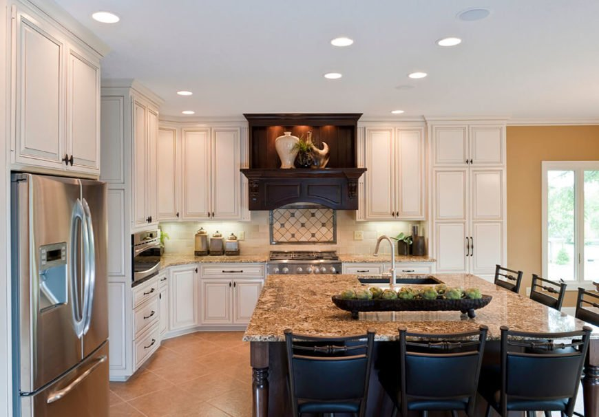 Dark wood successfully breaks up the use of white cabinetry against the tan backdrop created by the floor and walls. Dark chairs continue to ground the space and pops of bright green bring bits of color and life, carrying the eyes around the rest of the room.