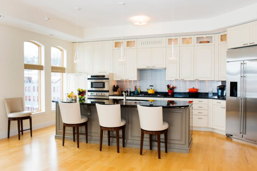 Creamy cabinets match the wall color in this open kitchen design. The designers used the bright white tiles of the backsplash to add a difference in color and a black countertop to break up the space. The warm gray of the island helps to differentiate it from the uniform counters.